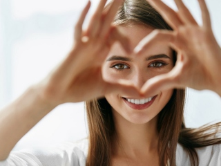 手をハートの形にして目をクローズアップしている女性の画像