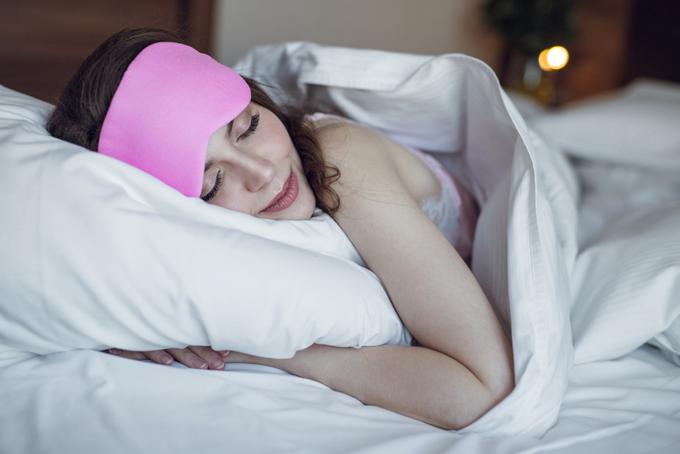 ベッドの上で枕を抱えて寝ている女性