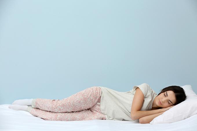 横向けで寝ている女性の画像