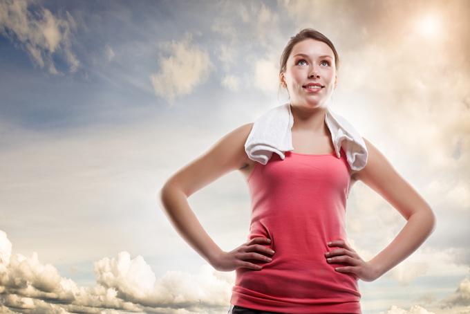 トレーニングウェアを着て腰に手を当てた女性の画像