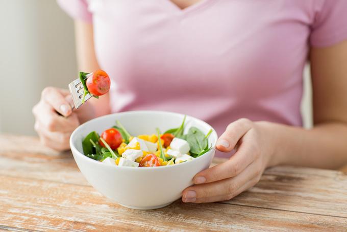 野菜をおいしそうに食べている女性の画像