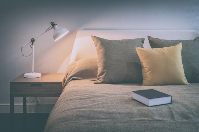 本が置かれたベッドとベッドサイドのランプの画像