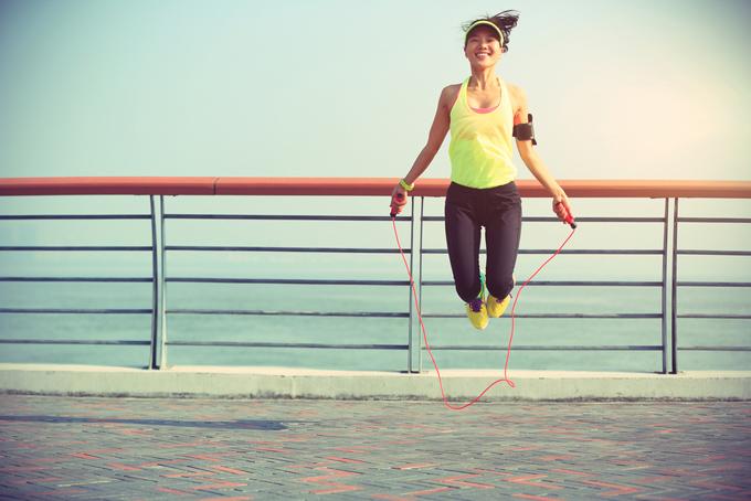 縄跳びで高く飛んでいる女性の画像