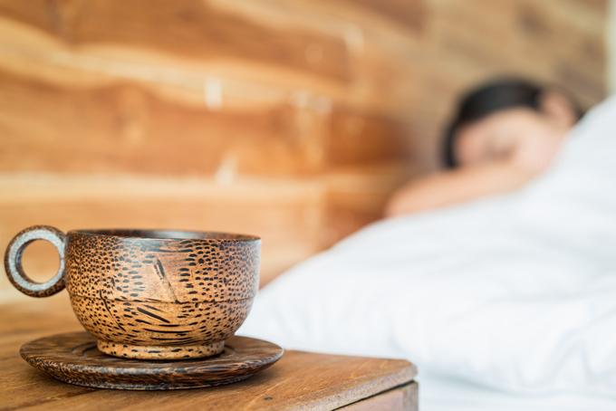 コーヒーを枕元に置き寝ている女性の画像