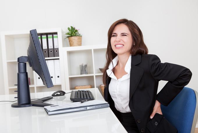 不調を抱えながらデスクワークする女性の画像