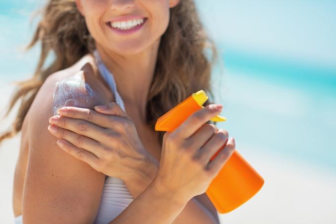 肩に日焼け止めを塗る女性の画像