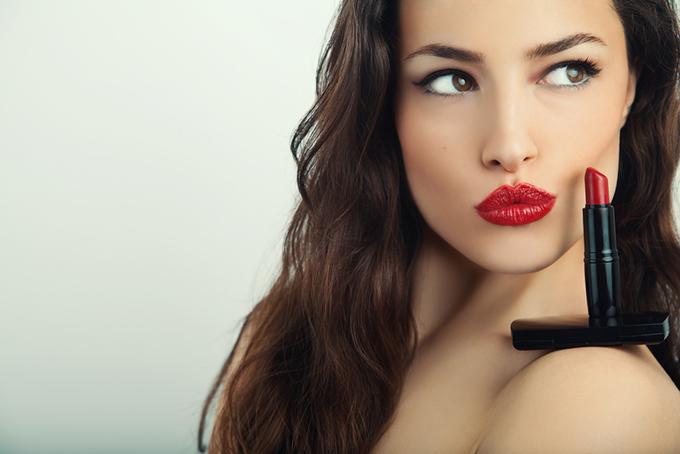 真っ赤な口紅を塗った女性と口紅の画像
