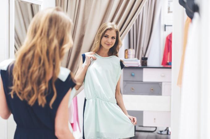 ワンピースを自分に合わせ、鏡を見る女性