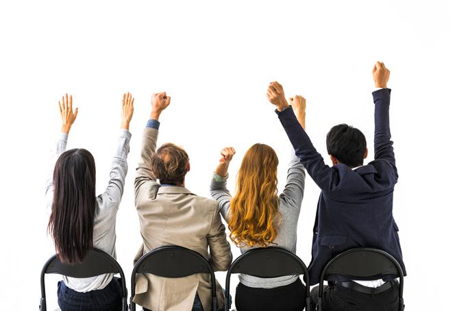 4人の男女が椅子に座って両手をあげている画像