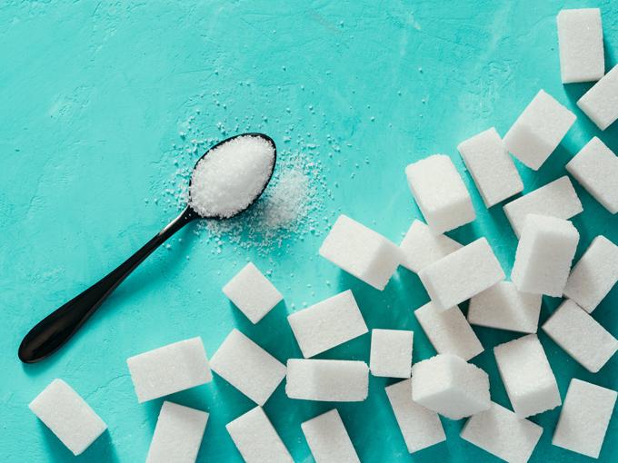スプーンに盛られた砂糖と大量の角砂糖の画像