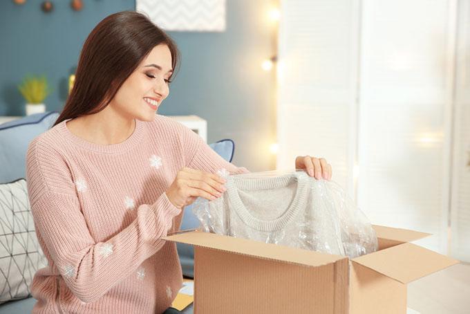 段ボール箱から洋服を取り出している女性の画像