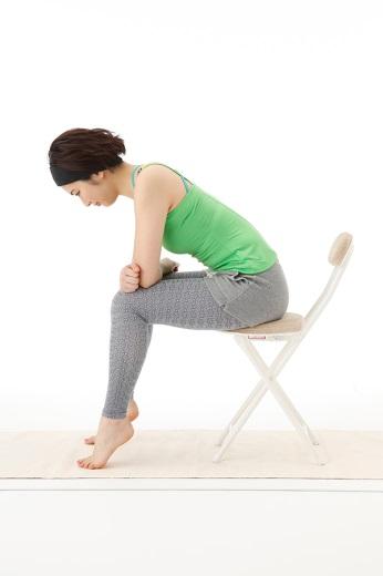 イスに座ったままひざに体重をかけてかかとを上げる写真