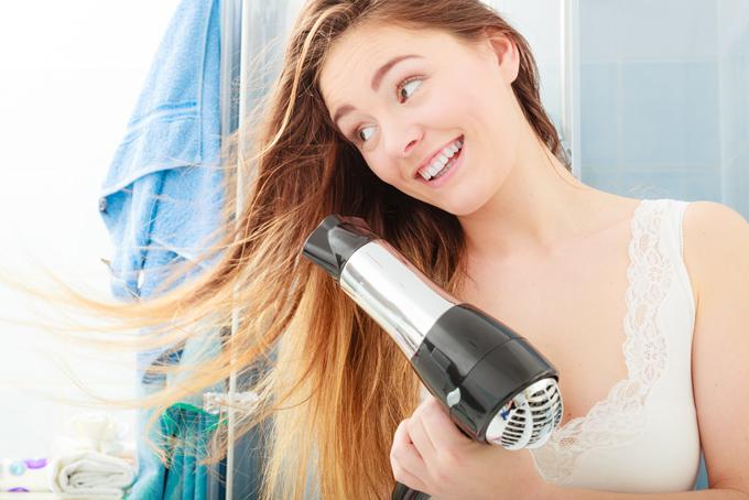 ドライヤーで髪の毛を乾かす女性の画像
