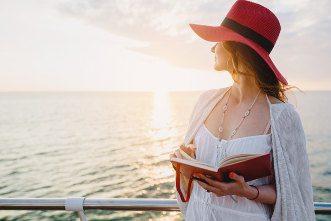 本を片手に海を眺める女性