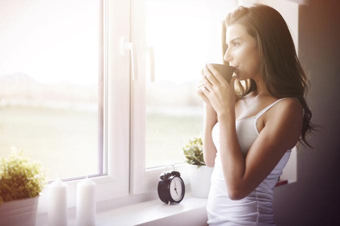 窓辺でコーヒーを飲む女性