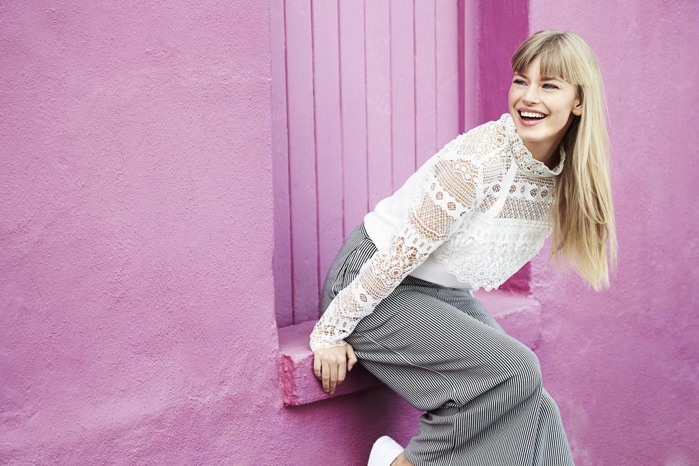 紫の壁の前で微笑む女性