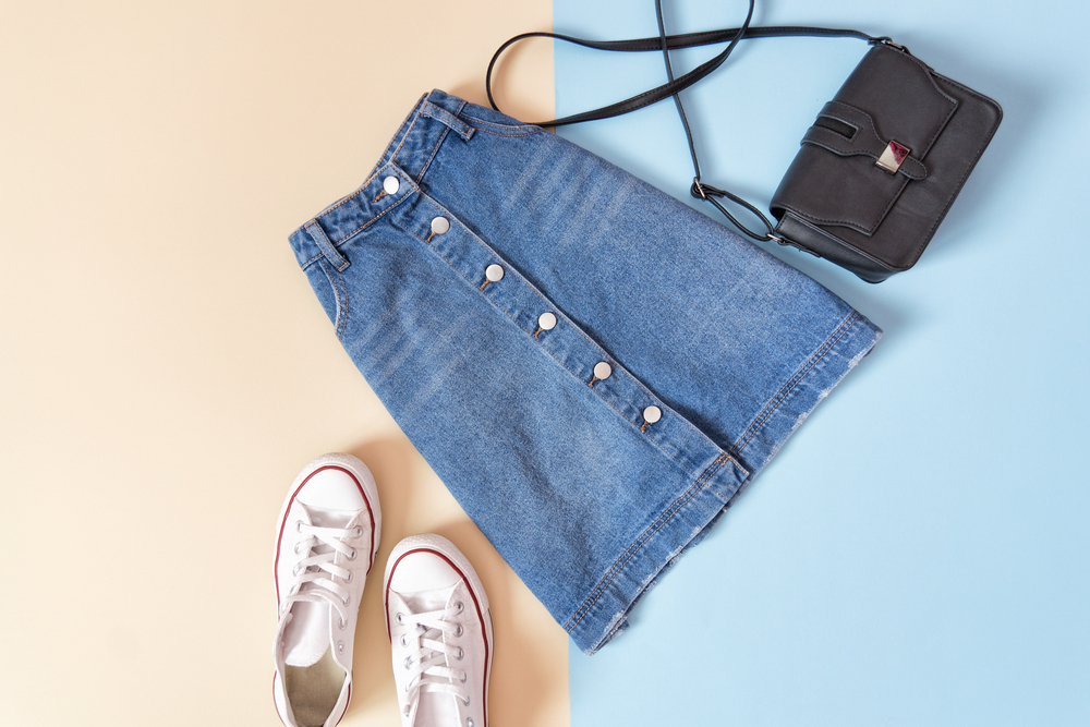 カラフルな床に置かれたデニムスカート、バック、スニーカー