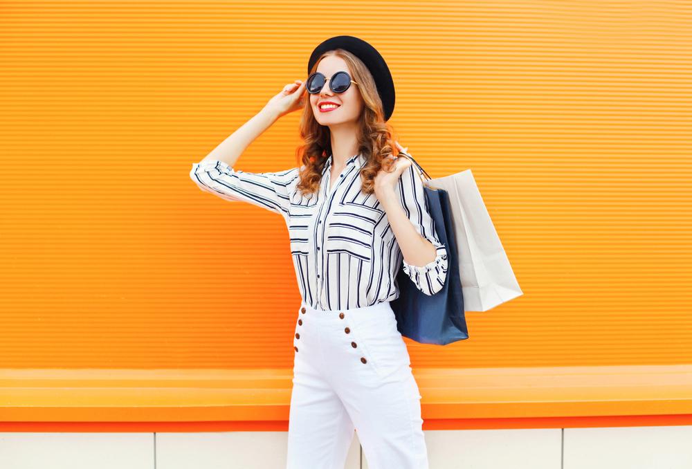 鮮やかなオレンジの壁の前に立つサングラスをかけた女性