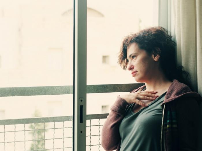 窓辺でゆううつそうな女性
