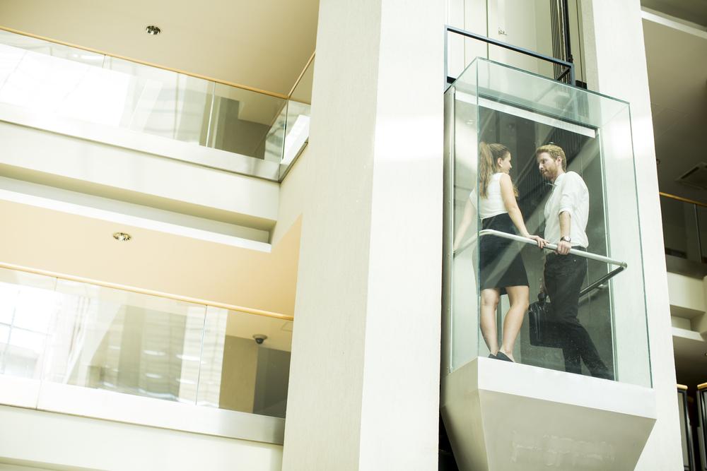エレベーターでのぼっていく男女