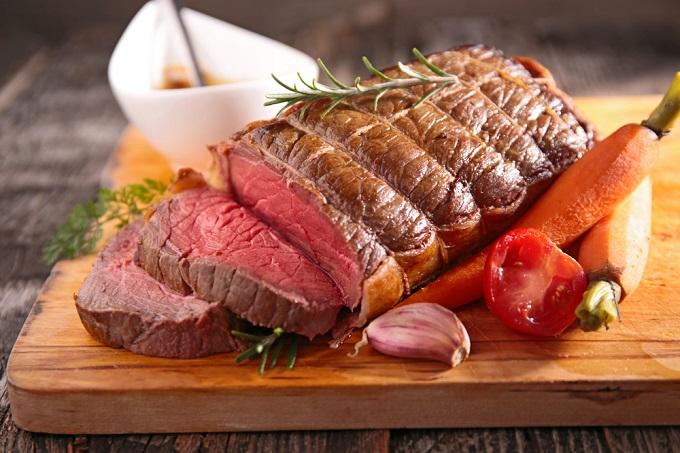 調理済みの牛肉の塊がまな板の上に乗っている