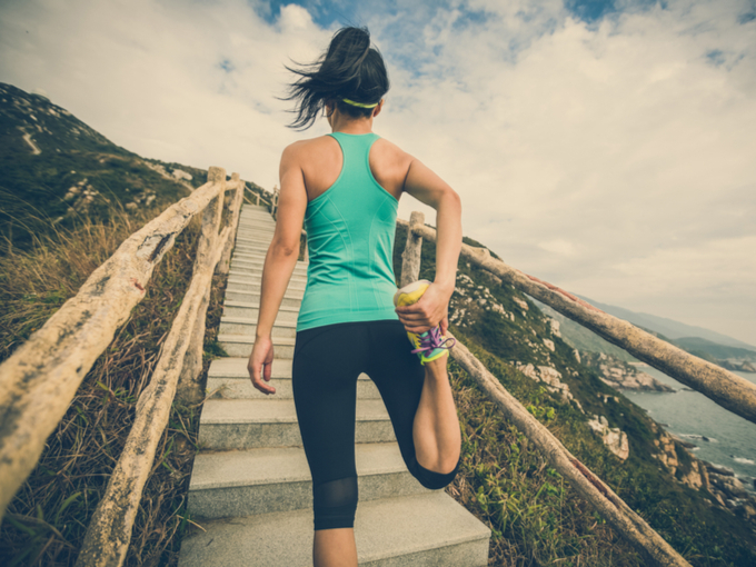 スポーツウェアの女性が階段を前に立つ写真