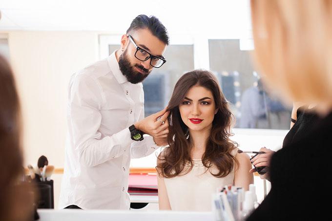 女性のヘアスタイルを整える男性の画像
