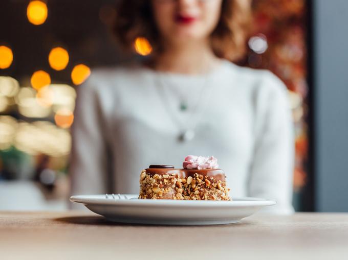 ケーキを前にガマンする女性