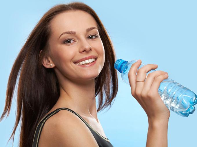 水のペットボトルを片手に笑顔の女性