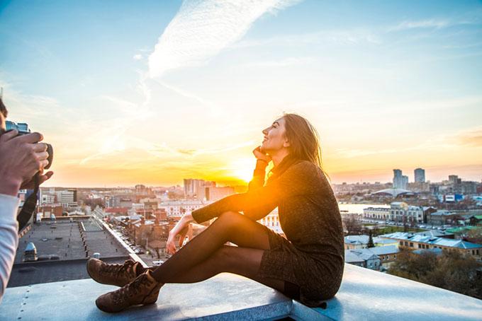 空の見える屋上で黒いストッキングを履いたモデル女性