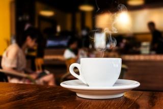 カフェのテーブルに置かれたコーヒーカップの画像
