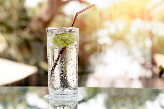 瓶からコップに炭酸水を注いでいる画像