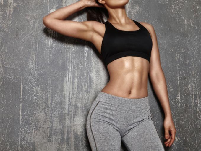 筋肉を美しく見せるようポージングをする女性