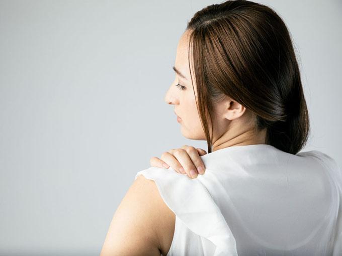 肩を抑える女性の画像