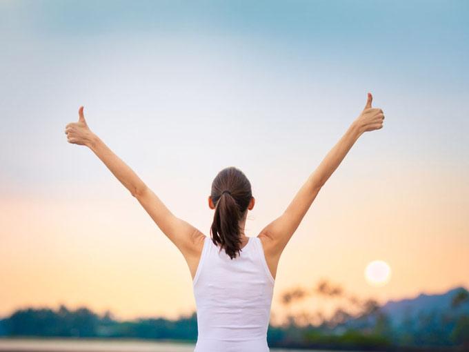両手の親指を立ててGOODサインを作る女性の画像