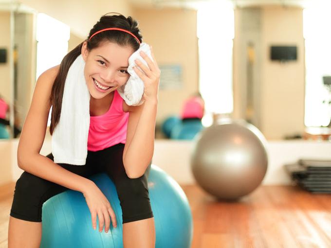 バランスボールの上で汗を拭う女性の画像