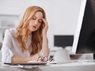 パソコンの前で疲れた顔をしている女性の画像