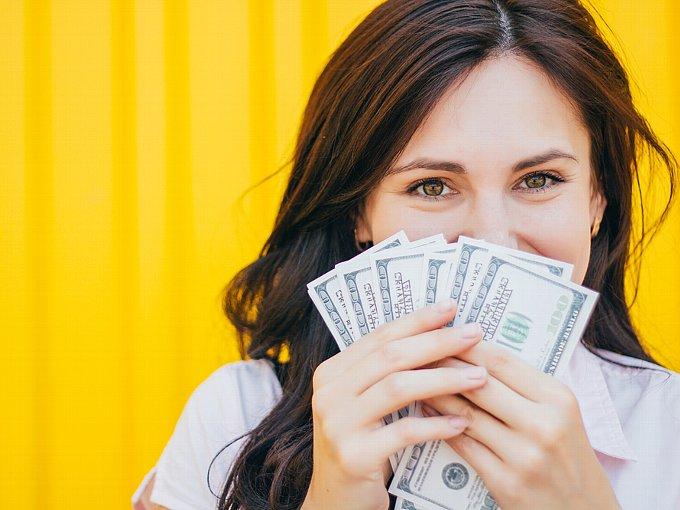 お札を顔に近づけて微笑む女性