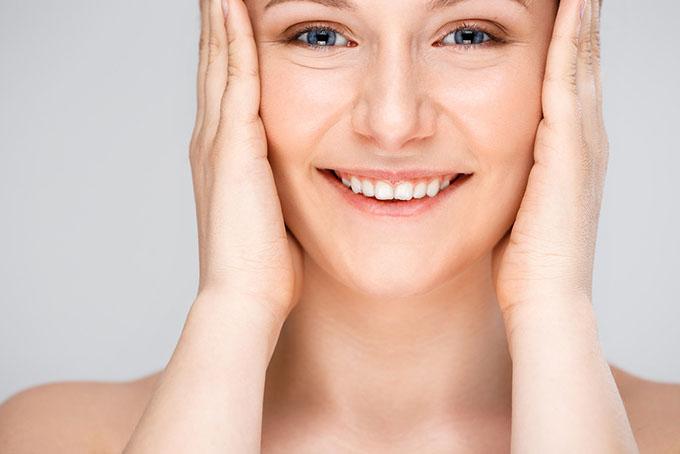 顔の横に手を当てている笑顔の女性の画像
