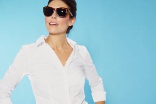 サングラスをかけた女性が白いシャツを着ている