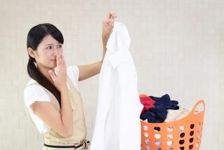 シャツを手にして鼻を抑えている女性の画像