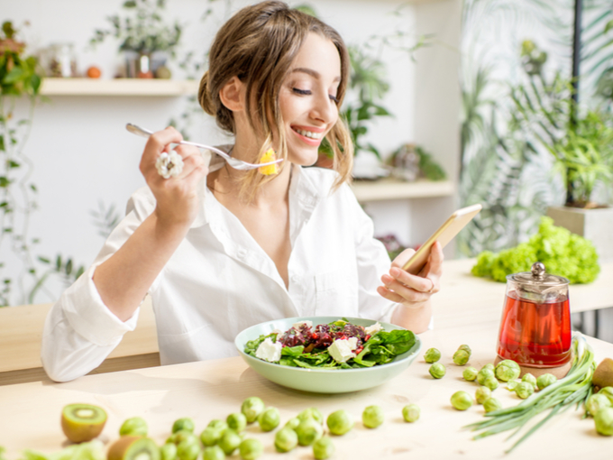 食事中の女性がスマホをチェックしている画像