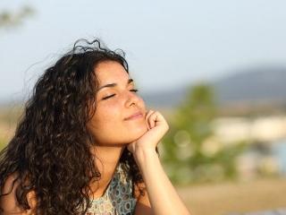目をつむり、風を感じる女性