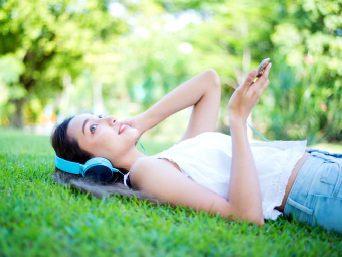 芝生の上で寝転がる女性の写真
