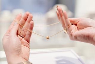 金のネックレスを手に持っている画像