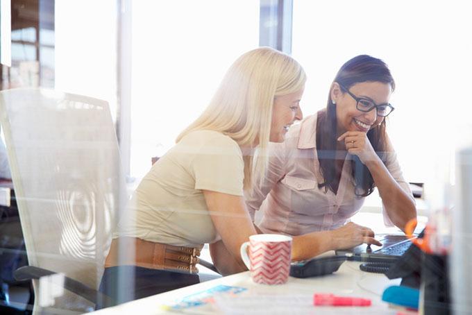 女性2人がパソコンの前で話をしている画像