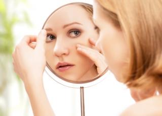 鏡をのぞき込んでいる女性の画像