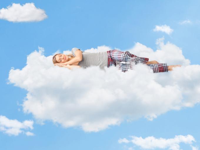 雲の上で眠っている女性の画像