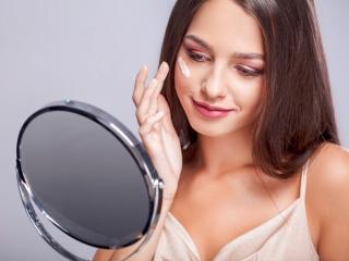 鏡を見ながらコンシーラーを塗る女性