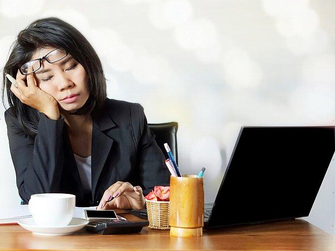 仕事中、眠りにつく女性
